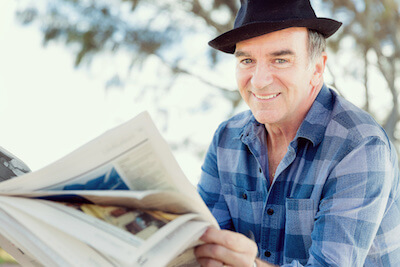 Elderly man smiling reading the newspaper